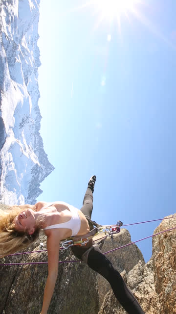 Young woman performs 'vertical' yoga moves, on climbing rope