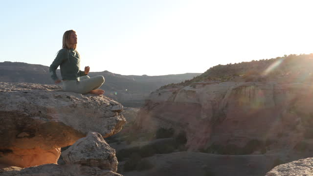 young woman performs yoga moves at sunrise - cross legged stock videos & royalty-free footage