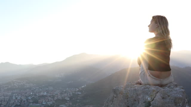 Young woman performs yoga moves, on rock above sea