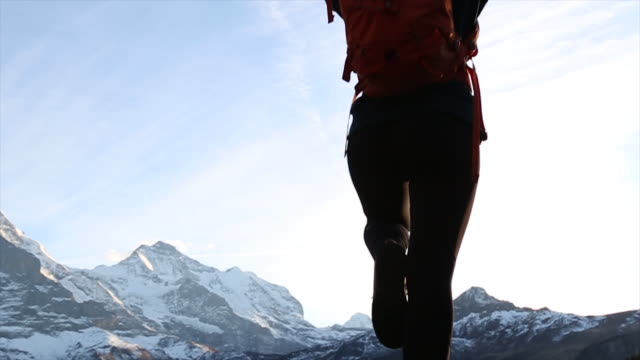 young woman performs yoga position in front of a majestic mountain backdrop - auf einem bein stock-videos und b-roll-filmmaterial