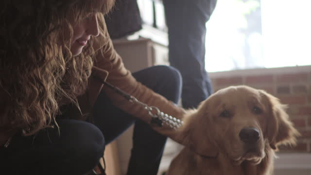 Young woman pets dog and laughs with boyfriend in hip downtown clothing store.