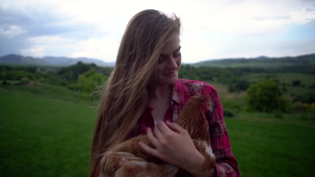 CU Young woman petting a chicken on a farm