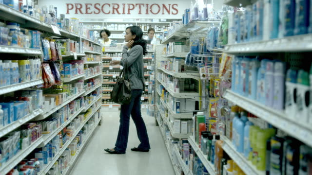 vídeos de stock, filmes e b-roll de ws, young woman pharmacy medicine aisle, scotch plains, new jersey, usa - prateleira mobília