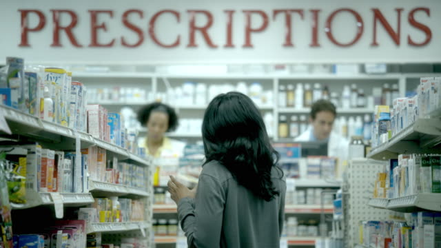 ms, r/f, young woman pharmacy medicine aisle, two pharmacists in background, scotch plains, new jersey, usa - shelf stock videos and b-roll footage