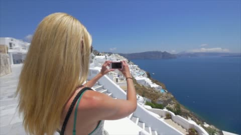 a young woman photographer taking photos traveling in santorini, greece, europe. - santorini stock videos & royalty-free footage