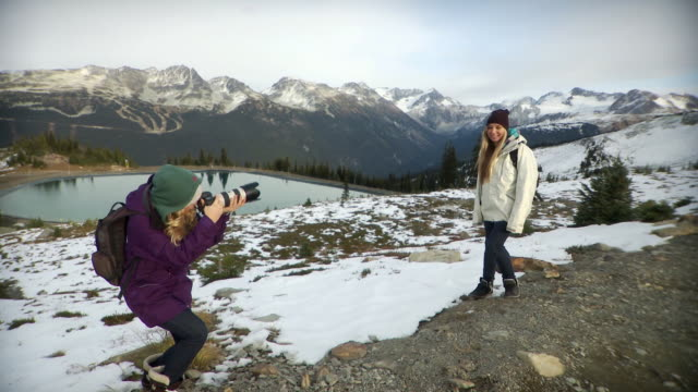 ws tu young woman photographing friend on whistler mountain / whistler, british columbia, canada  - snapping stock videos & royalty-free footage