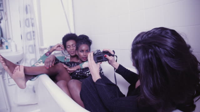 young woman photographing friends in bathtub at party - fotograf stock-videos und b-roll-filmmaterial