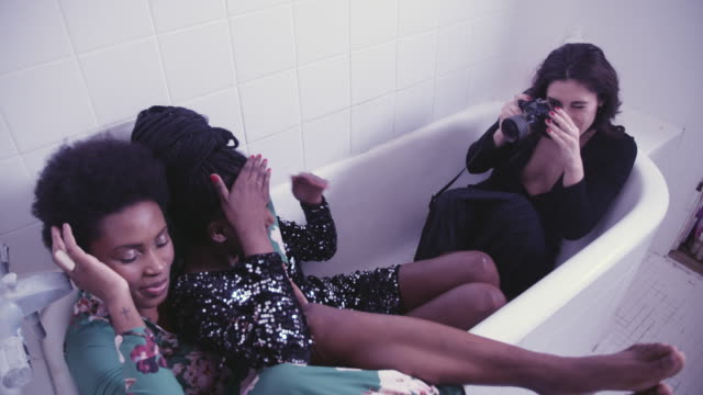 young woman photographing friends in bathtub at party - kleid stock-videos und b-roll-filmmaterial