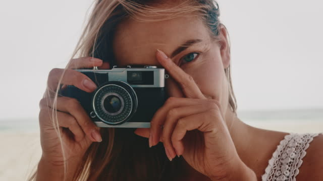 young woman photographing through vintage camera - persona attraente video stock e b–roll
