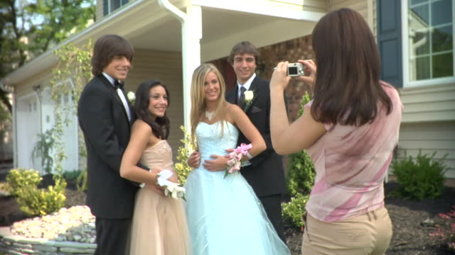 MS, Young woman photographing two couples in prom attire in front of house, portrait, Edison, New Jersey, USA