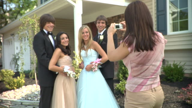 vídeos de stock e filmes b-roll de ms, young woman photographing two couples in prom attire in front of house, portrait, edison, new jersey, usa - formal garden