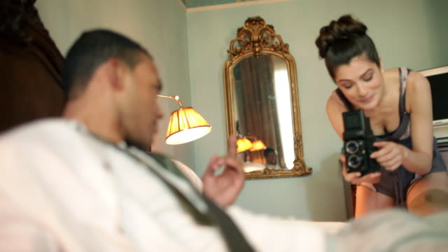 young woman photographing young man on bed - kamisol stock-videos und b-roll-filmmaterial
