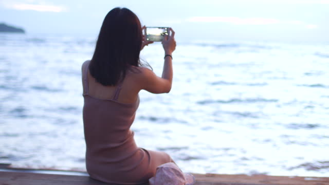 Young woman photographs ocean view