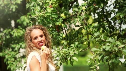 vídeos y material grabado en eventos de stock de mujer joven recolección y comer una manzana - mujer bella