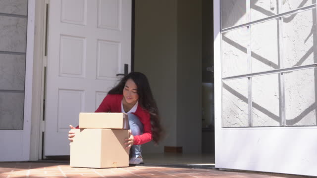 ws young woman  picking up boxes delivered to her door - cardigan sweater stock videos & royalty-free footage