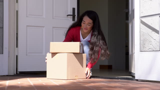 ws young woman picking up boxes left at her door. - köpa online bildbanksvideor och videomaterial från bakom kulisserna