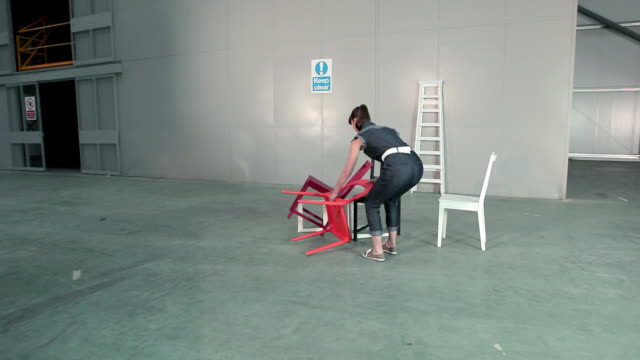 young woman picking up chairs and placing on floor - short phrase stock videos & royalty-free footage