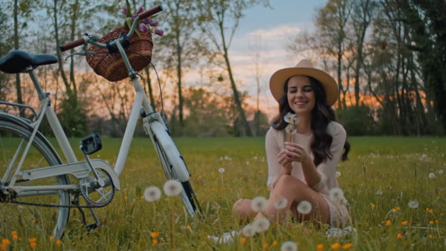 vídeos y material grabado en eventos de stock de slo mo ws pan mujer joven recogiendo dientes de león en prado - cesta de picnic