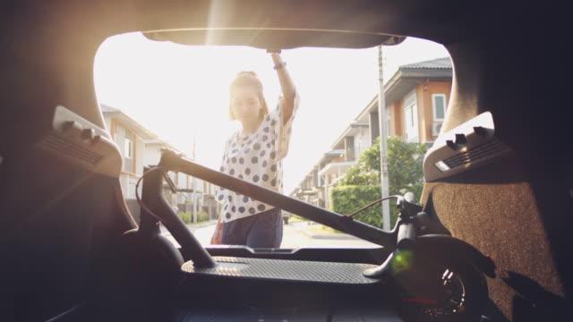 vídeos y material grabado en eventos de stock de mujer joven recogiendo scooter eléctrico preparándose para el viaje por carretera - maletero