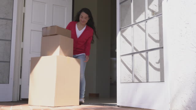 ws young woman picking up many packages left at her door - package stock videos and b-roll footage