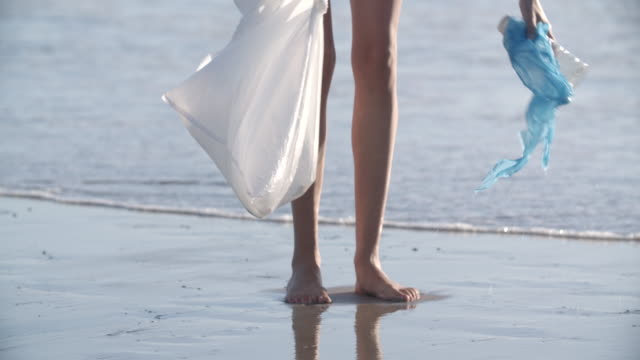 young woman picking up rubbish on the beach - water pollution stock videos & royalty-free footage