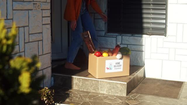 vídeos y material grabado en eventos de stock de slow motion mujer joven recogiendo la caja de comida desde la puerta - super slow motion