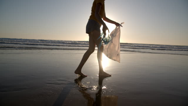 vídeos de stock, filmes e b-roll de young woman picking up trash on the beach at sunset - reciclagem