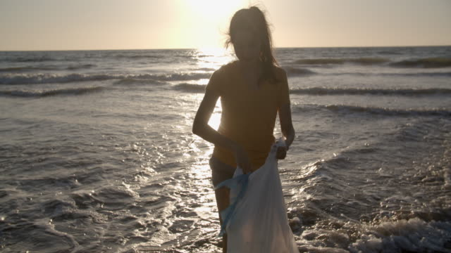 young woman picking up trash on the beach at sunset - picking up stock videos & royalty-free footage
