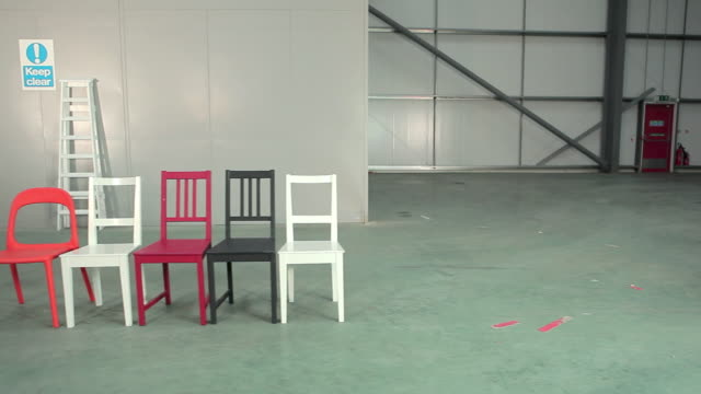 young woman placing cushions on chairs - chairs in a row stock videos & royalty-free footage