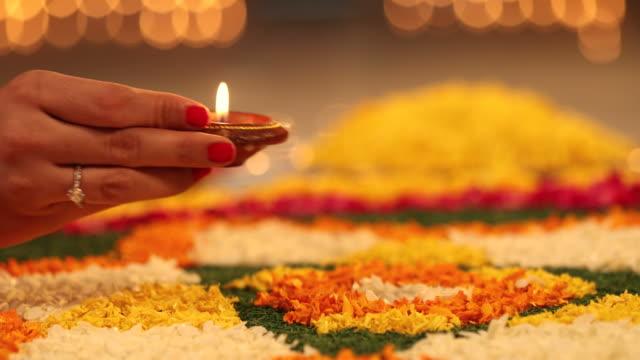 CU Young woman placing diya on flower petals rangoli during Diwali festival / New Delhi, Delhi, India