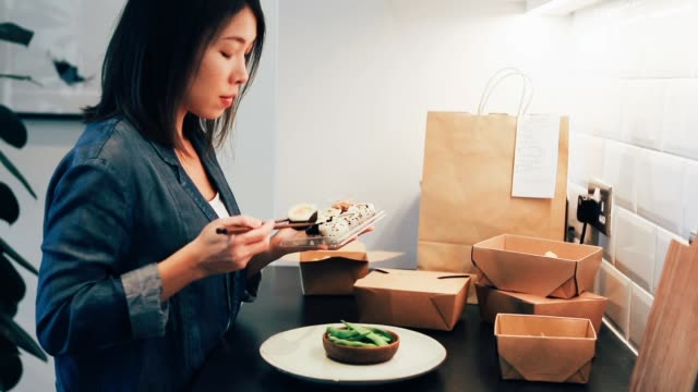 young woman placing takeaway sushi on the plate - gourmet stock videos & royalty-free footage