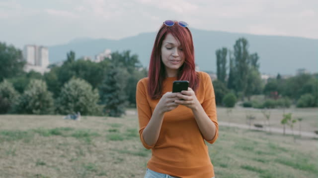 young woman playing a game outdoors. - contented emotion stock videos & royalty-free footage