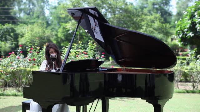 young woman playing a piano  - ピアノ点の映像素材/bロール