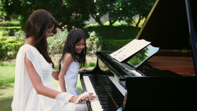 young woman playing a piano with a girl  - piano stock videos & royalty-free footage