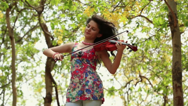 Young woman playing a violin in the park, Delhi, India