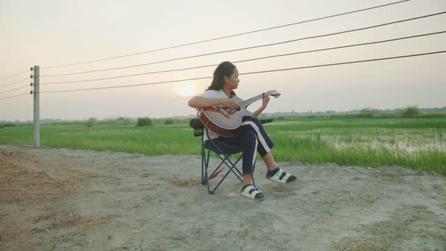 junge frau spielt akustikgitarre in der natur - gitarre stock-videos und b-roll-filmmaterial