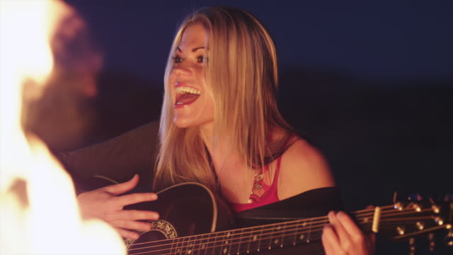 ms young woman playing guitar and singing at campfire at dusk / lake powell, utah, usa - lake powell stock videos and b-roll footage