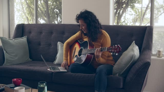 vidéos et rushes de ms young woman playing guitar at home - instrument de musique