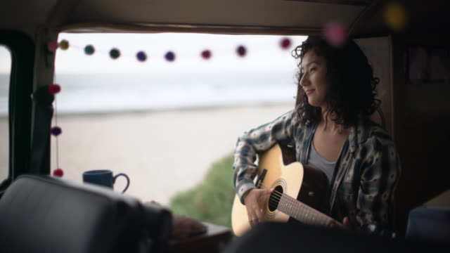 Young woman playing guitar in her camper van by the beach