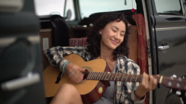 Young woman playing guitar in her camper van