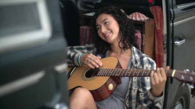young woman playing guitar in her camper van - キャンプする点の映像素材/bロール