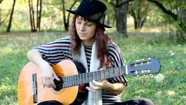 Young woman playing guitar on summer day in park outdoors.