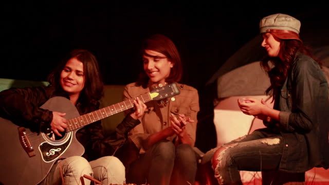 Young woman playing guitar with her friends in the forest, Delhi, India