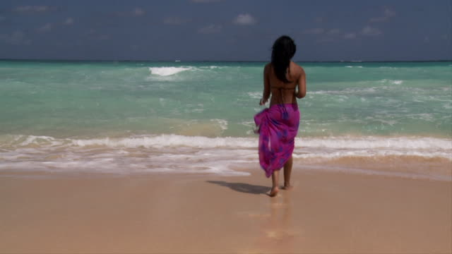 SLO MO, WS, Young woman playing in ocean waves, Punta Cana, Dominican Republic