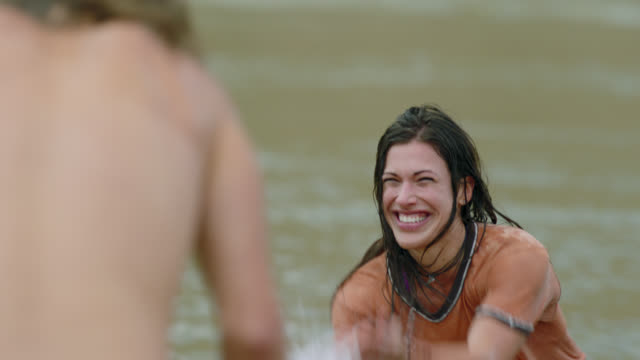 vídeos de stock, filmes e b-roll de young woman playing in river splashes man with cold water and laughs. - vadear