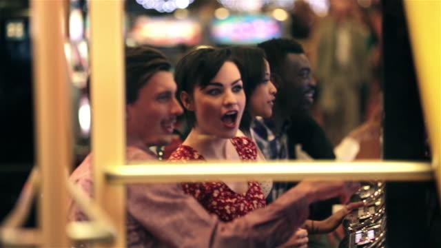 vídeos y material grabado en eventos de stock de young woman playing slots in vegas casino hits jackpot, celebrates with friends - máquina con ranura