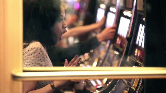young woman playing slots in vegas casino hits jackpot, celebrates with friends - kasino stock-videos und b-roll-filmmaterial