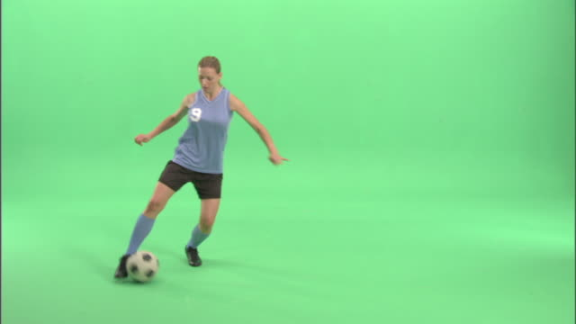 ws, young woman playing soccer in studio - soccer player stock videos & royalty-free footage