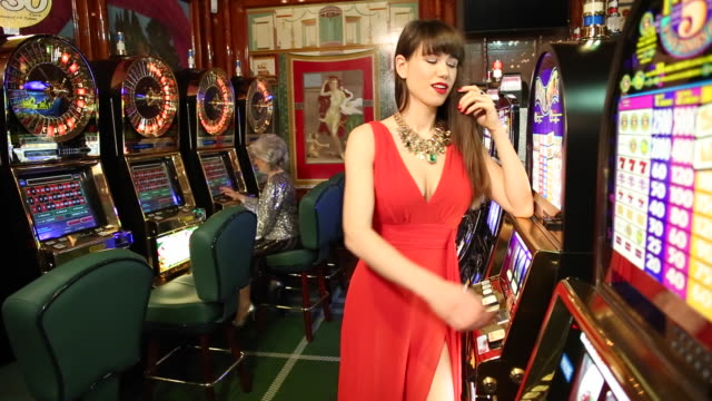 Young woman playing the slot machine in a casino.