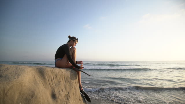 ws young woman playing with a shell by the sea - schnorcheln stock-videos und b-roll-filmmaterial